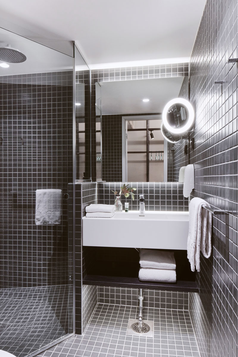 This modern hotel bathroom has dark tiles that contrast the bright white vanity. #ModernBathroom #DarkTiles