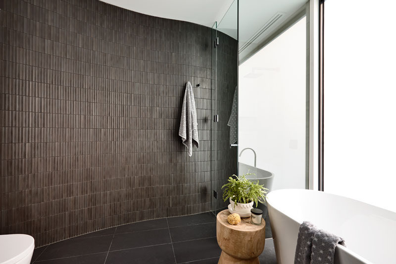 This modern bathroom features a curved brown-tiled wall that continues through into the shower, that's somewhat hidden behind a mirror. Click through to see more photos of this modern house. #ModernBathroom #BrownTiles #BathroomDesign
