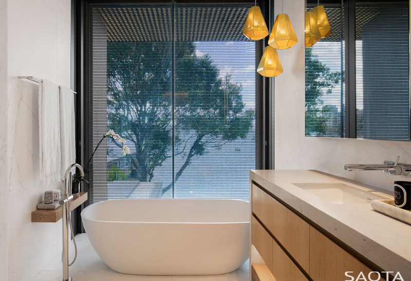 In this modern bathroom, the freestanding bathtub sits next to the window and has harbour views. #ModernBathroom #BathroomDesign