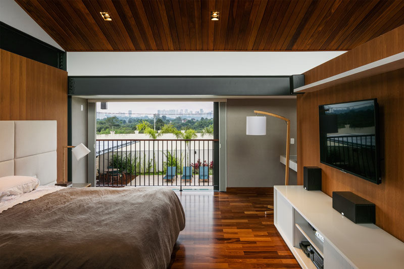 This modern bedroom has sliding doors that open to reveal a small balcony that overlooks the backyard and swimming pool below. #ModernBedroom #Balcony