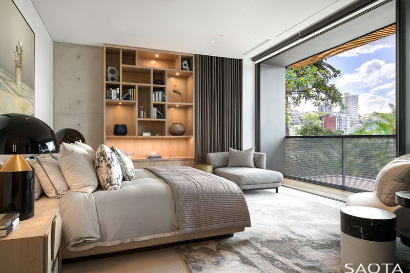 This modern bedroom has a sliding glass door that opens up to a small balcony. #ModernBedroom #WoodShelving #Balcony