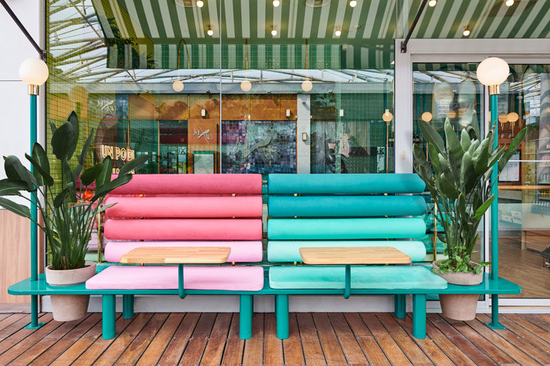 Colorful benches with bright cushions and planters sit outside this modern Italian restaurant. Click through to see more photos. #Seating #RestaurantDesgin #OutdoorSeating