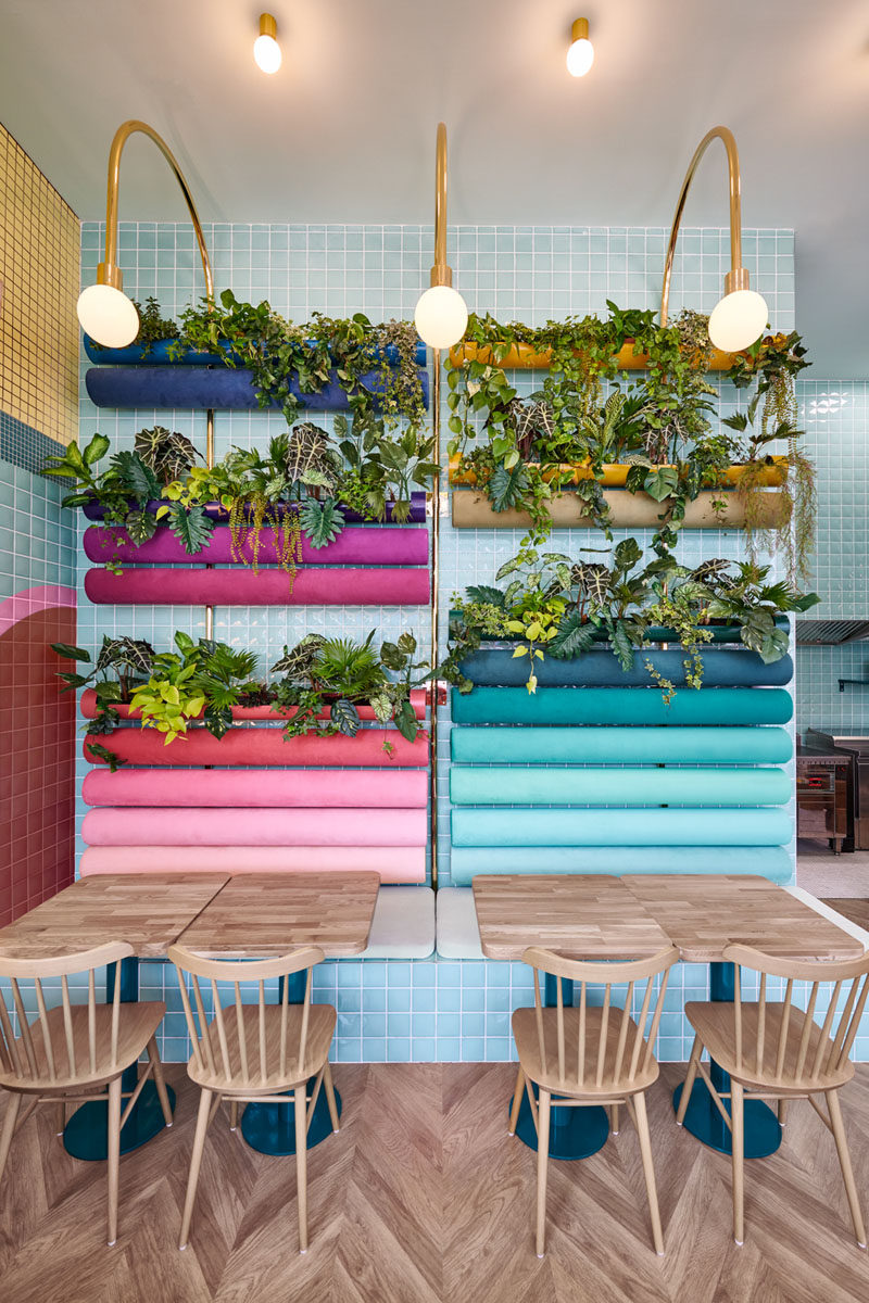 In this modern restaurant, plants have been added to the back 'rainbow' cushions on the wall in the seating area, while gold bar lamps curve over to add light to the space and tie in with the customer service area. Click through to see more photos of this interior. #RestaurantDesign #Planters #Seating #InteriorDesign