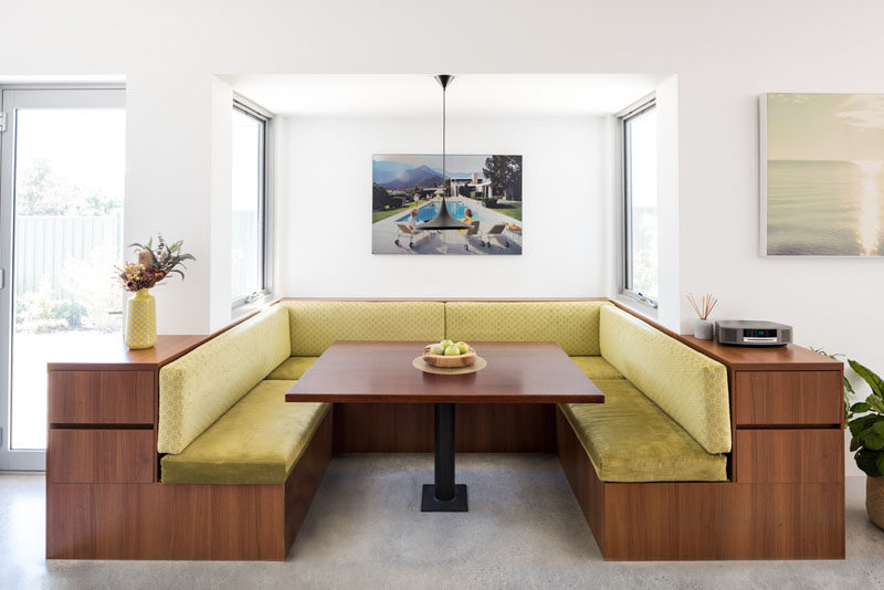 Drawing from mid-century design and American Diner styled breakfast booths, a custom booth was created this modern house, that acts as a natural hub for the family. #DiningBooth #ModernDining
