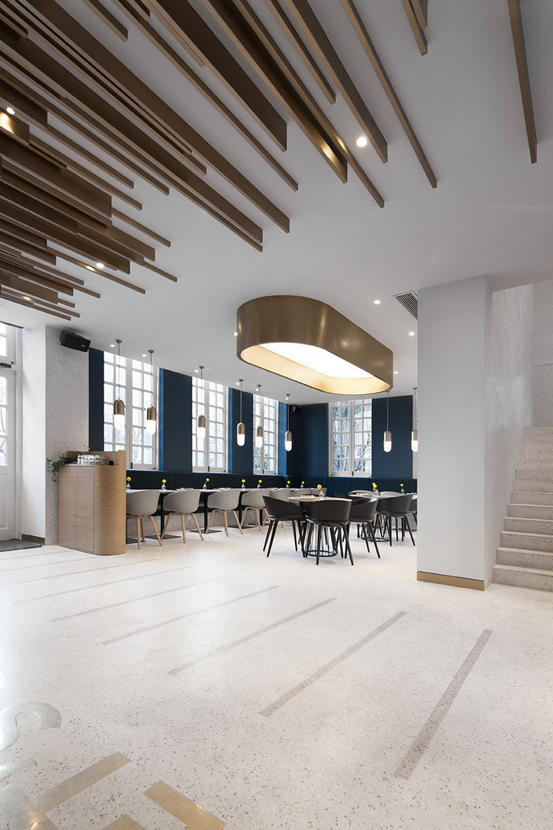 In this modern cafe, dark blue walls match the dark blue banquette seating that wraps around the seating area, creating a striking contrast to the white walls and ceiling. #ModernCafe #BlueAccentWalls