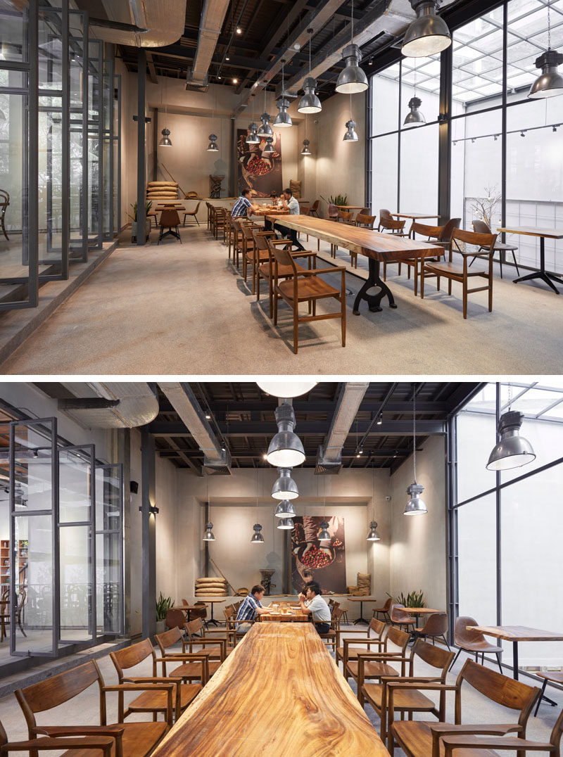 This modern coffee house a space set up for larger groups of people with a long 10 person table. Natural light from skylights above the garden filter through the black framed windows, that also provide a view of the garden below. #CoffeeHouse #CoffeeShop