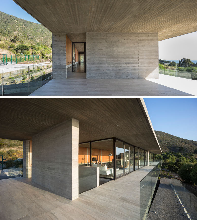 This modern house has a concrete wall with an opening that leads to the glass front door. Click through to see more photos of this concrete house. #ModernHouse #ConcreteHouse