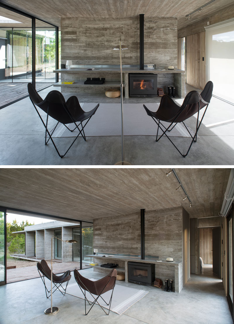Inside this modern house, board formed concrete has been used for the walls, ceiling and shelving elements, while large floor-to-ceiling windows and sliding glass doors allow natural light to flood the interior of the home. #BoardFormedConcrete #Fireplace #LivingRoom