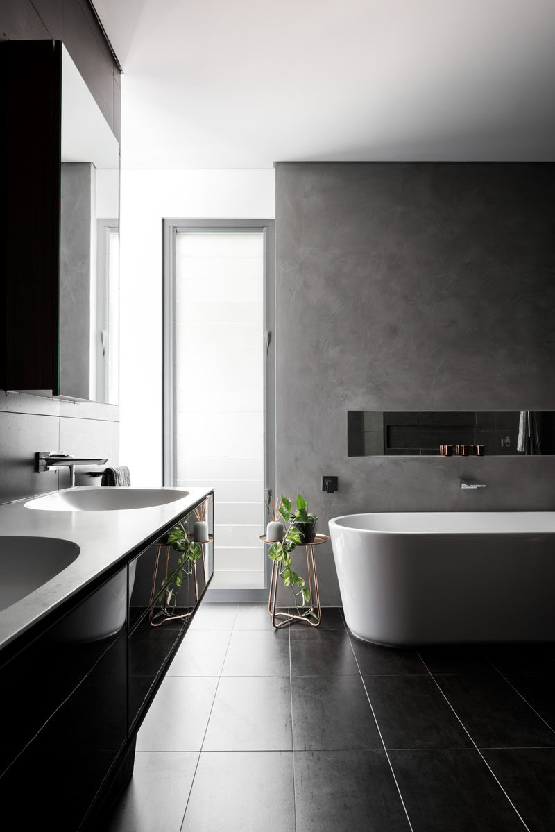 In this modern bathroom, a black vanity matches the tiles, while the white counter matches the freestanding bathtub, and a grey accent wall provides a backdrop for the bath and allows for a small shelf and mirror. #ModernBathroom #BlackAndWhite