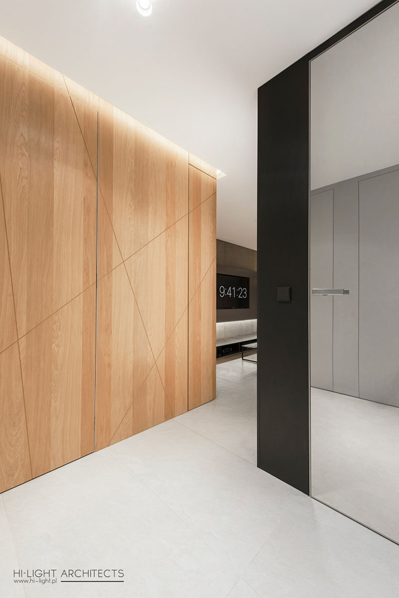 Stepping inside this modern apartment, the front door almost blends away into the wood accent wall with hidden lighting, while a black box leads into the living room. #WoodAccentWall