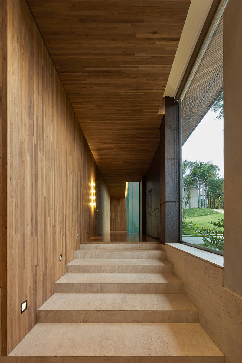 Just inside the front door of this modern house is a hallway that's covered in wood, and that leads to the different levels of the house. #Hallway #Entryway