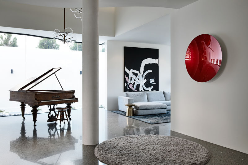 This foyer has a 2-storey atrium space that literally cuts through the house forming a formal lounge and piano room. Click through to see more photos of the house. #ModernFoyer #InteriorDesign #FormalLounge