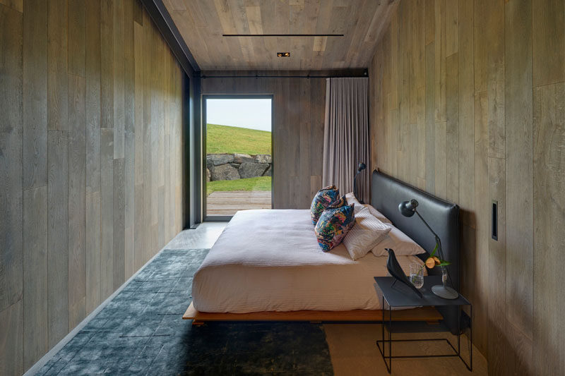 In this modern guest bedroom, there's wood walls and ceilings, a concrete floor with a blue rug, and a glass door that frames the view and opens to a small wood deck. Click through to see more photos of this modern guest house. #GuestHouse #Bedroom #WoodWalls #GlassDoor #ConcreteFloor #GuestBedroom