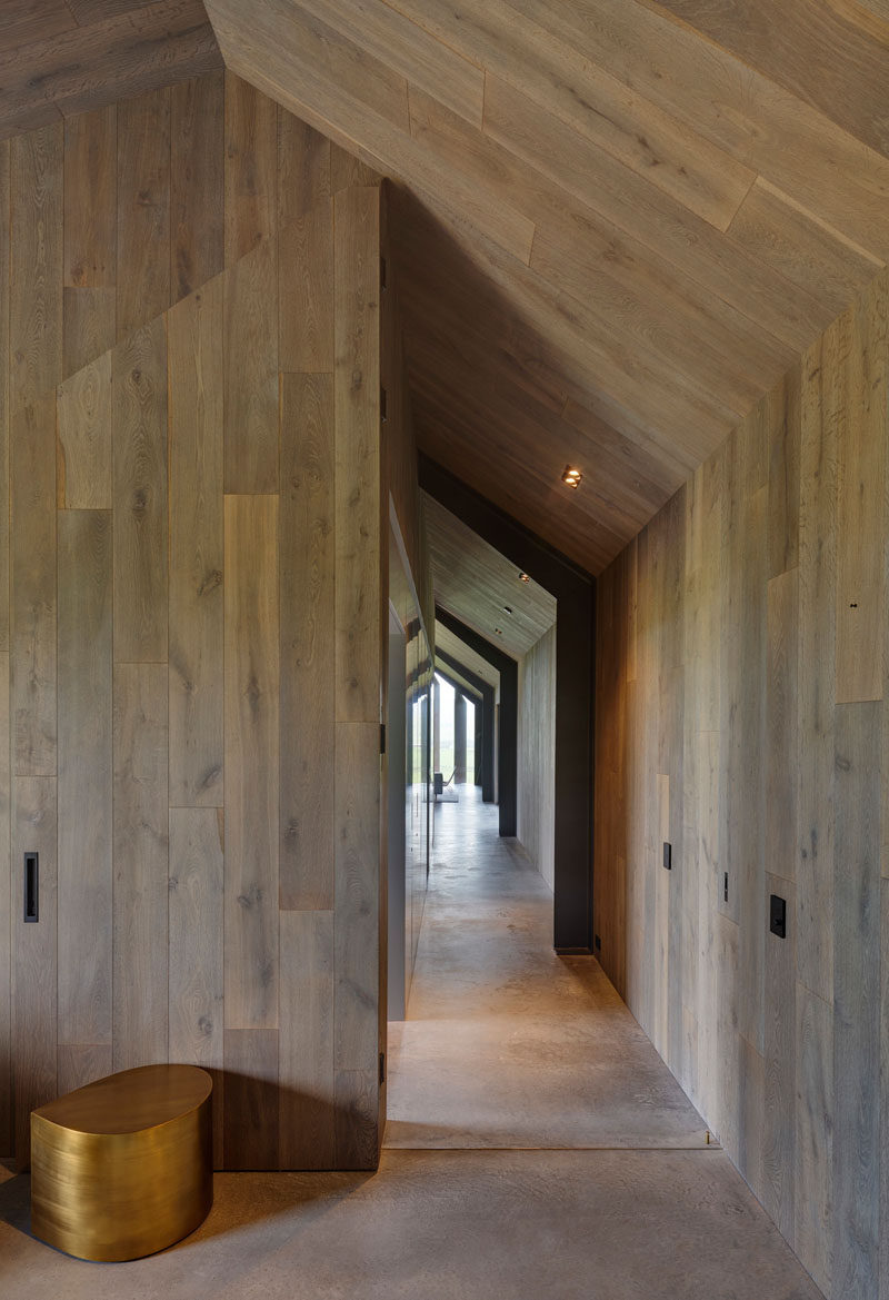 In this modern guest house, the hallway and ceiling is lined in wood, while the flooring is concrete. Click through to see more photos of the guest house. #Hallway #Wood #ConcreteFloor #InteriorDesign