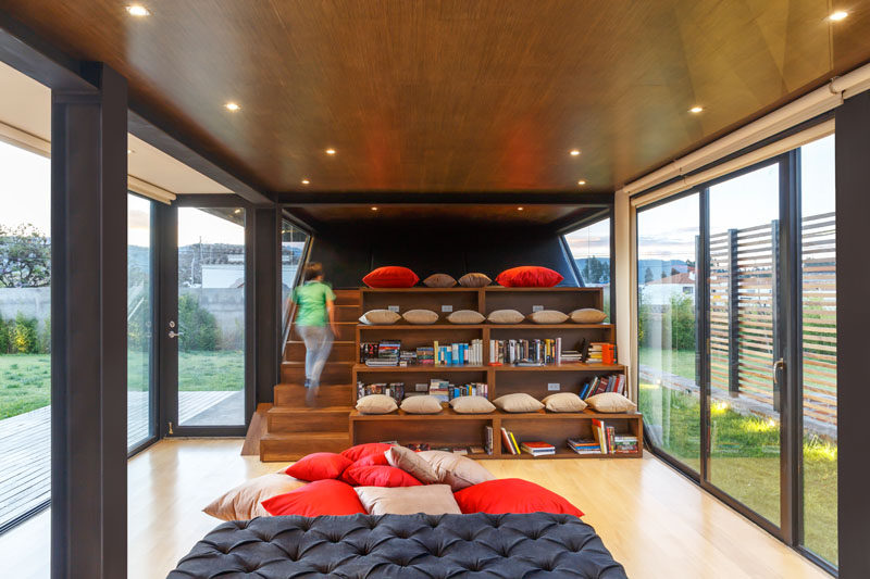 This modern house has a reading area with stairs and stadium seating. The wood stadium seating has open fronts for storing books and pillows. #HomeLibrary #Seating #InteriorDesign