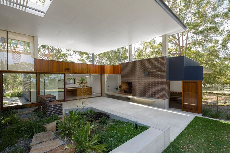 This covered outdoor space provides plenty of room for alfresco dining and relaxing in the shade. Click through to see more photos of this modern house. #OutdoorSpace #Landscaping