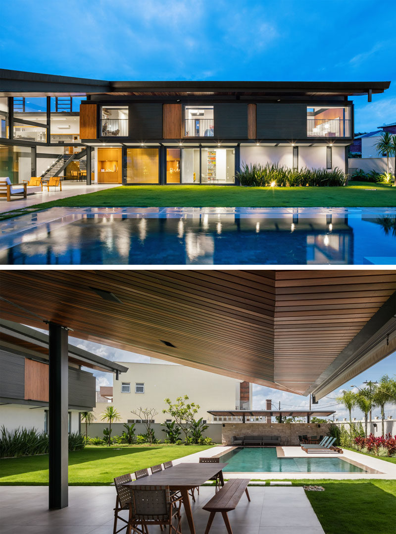 This modern house opens up to a grassy lawn with a swimming pool, while plants line the surrounding fence. There's also a cabana with outdoor lounge at the end of the pool. #Landscaping #SwimmingPool #Cabana