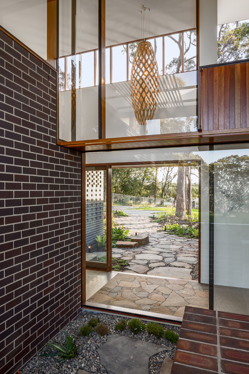 As this entryway has plenty of glass, the sliding glass front door allows for seamless views through to the backyard and outdoor space. Click through to see more photos of this modern house. #Windows #Entryway #FrontDoor