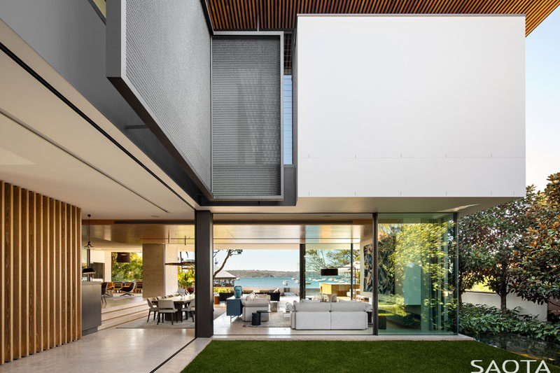 This modern house is designed in a U-shape with the interior spaces opening up to outdoor spaces, like a small grassy area that has shade from the house. #Modernhouse #Architecture