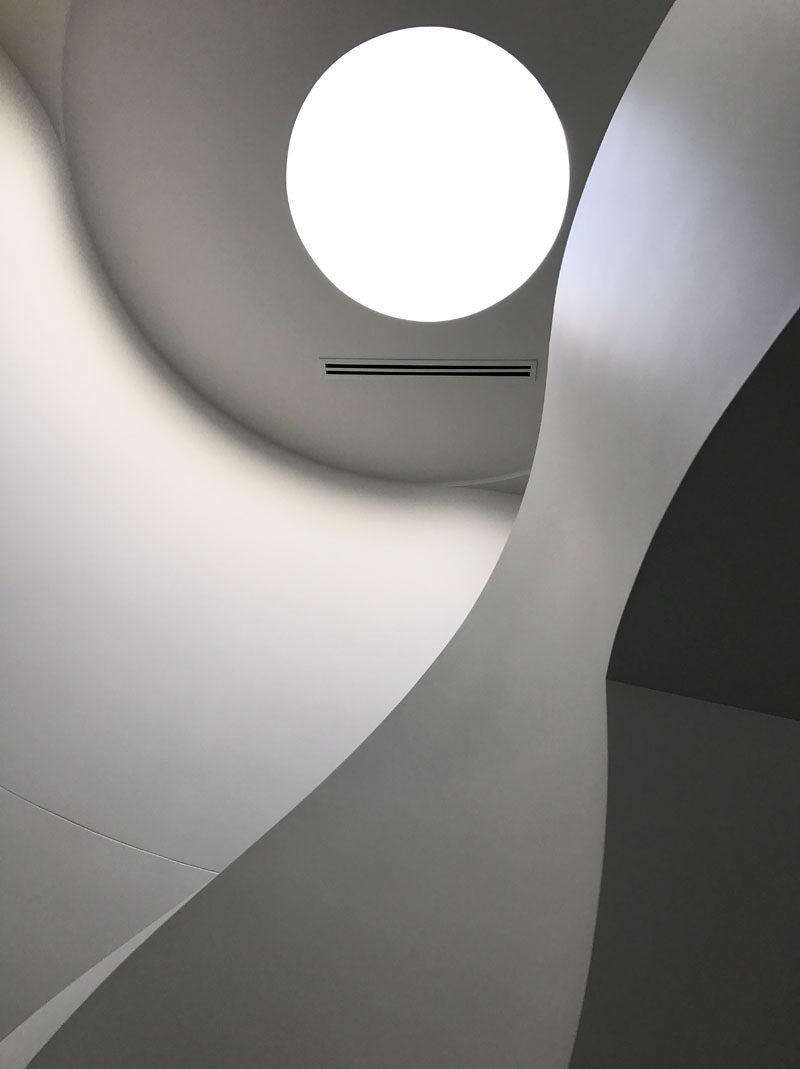 This modern house has a single round skylight that highlights the stairs. Click through to see more photos of this house. #Skylight #Architecture #Windows