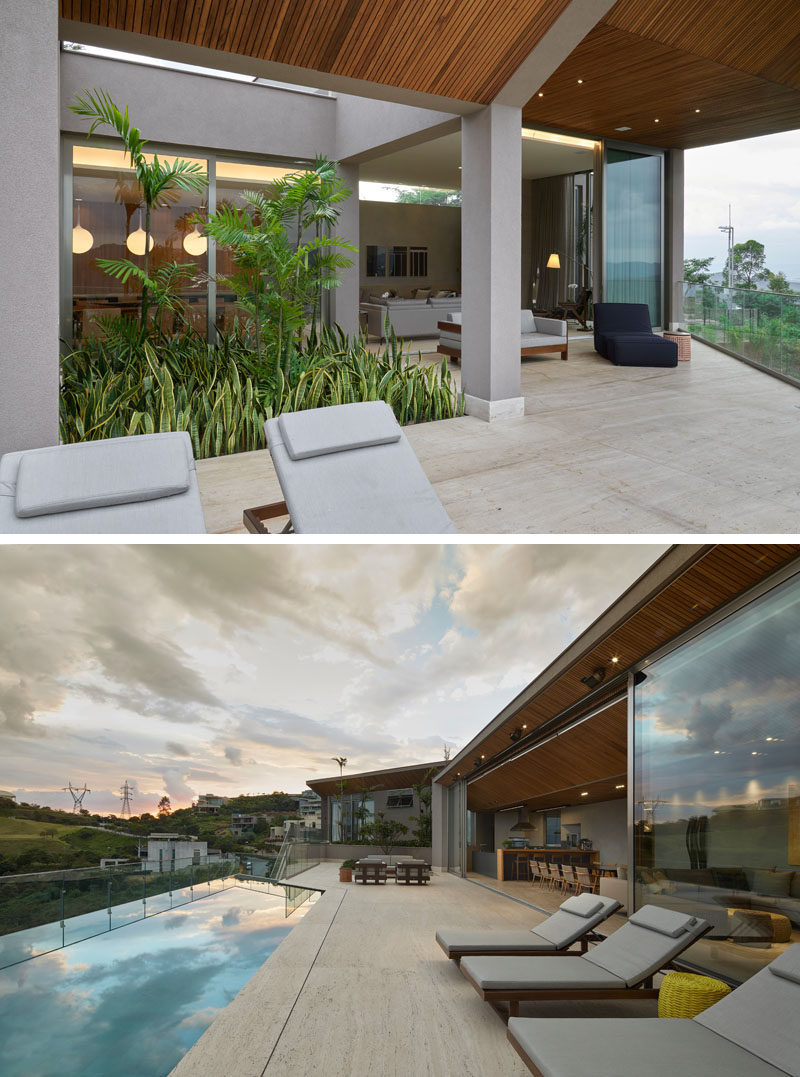 The living spaces of this modern house open up to an outdoor space with a variety of seating options and a swimming pool that looks out over the valley below. #SwimmingPool #Deck #ModernHouse