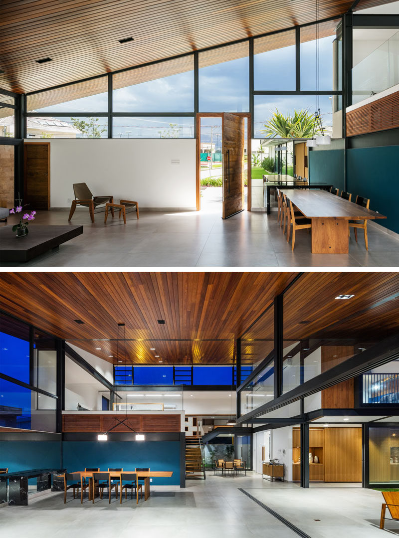 A pivoting wood front door welcomes visitors to this modern house, and once inside, there's a pop of blue in the dining area that contrasts the large wood ceiling and concrete floor. #ModernHouse #WoodCeiling #DiningTable