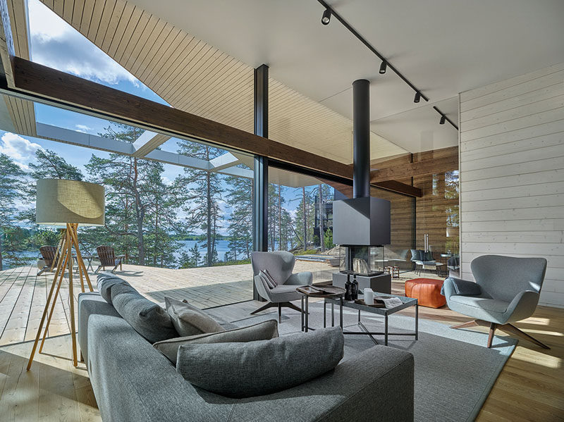 The interior of this modern house is bright and open with large glass walls, white walls and ceiling, and in the living room there's a fire for cool nights. #ModernLivingRoom
