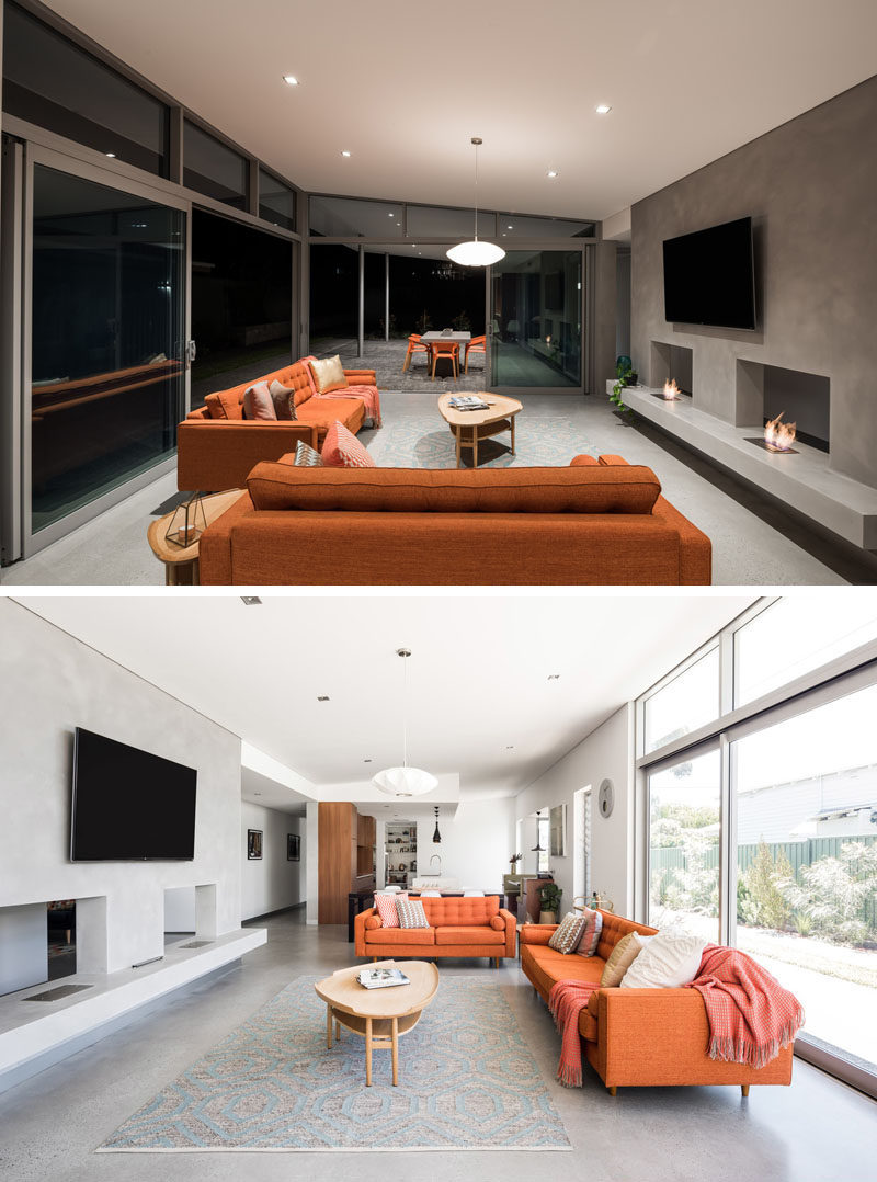 This modern house has an open living area with two fireplaces, that's flooded in daylight during the day and has a seamless integration with the outdoor living area by the carport. #ModernLivingRoom #Fireplace