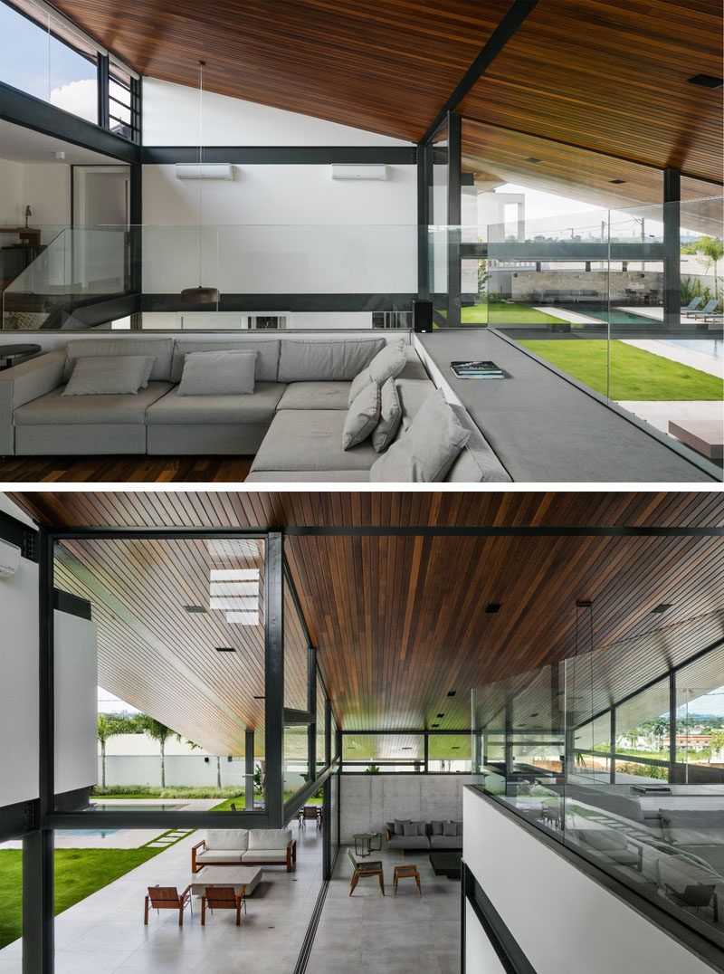 At the top of the stairs in this modern house, is a secondary lounge area, that has glass partitions to allow users to see the full wood ceiling and the spaces below. #LivingRoom #Ceiling #RoofLine