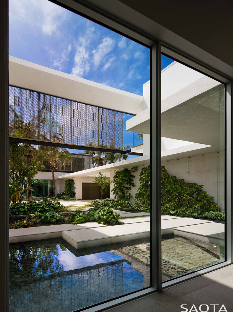 Large windows in this modern house provide a view of a water feature, garden and path. #Windows #Architecture