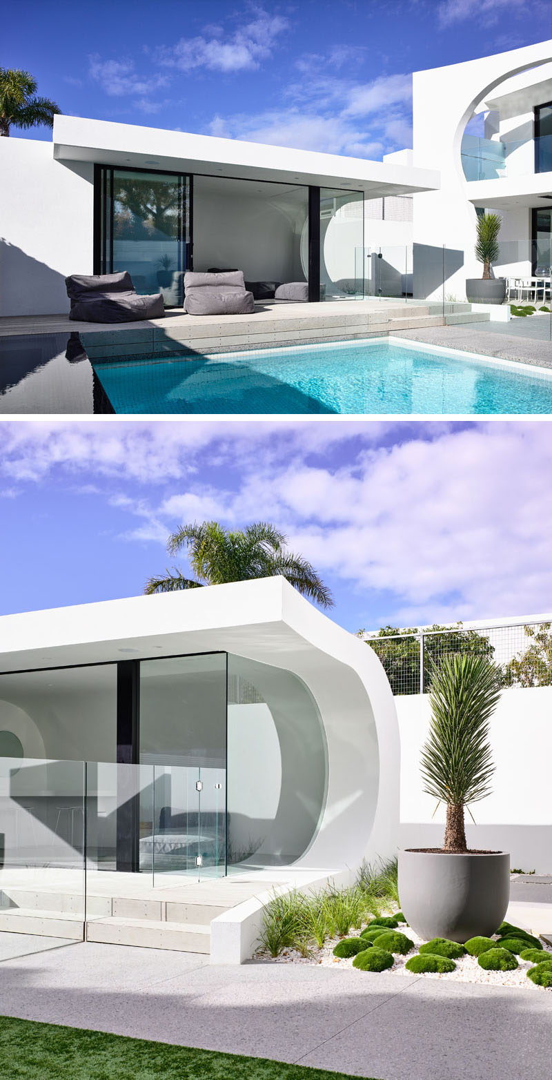 This modern backyard has aninfinity edge spa and pool, and a wave style pool house. Click through to see more photos of this modern house. #Pool #SwimmingPool #PoolHouse #Architecture #Cabana