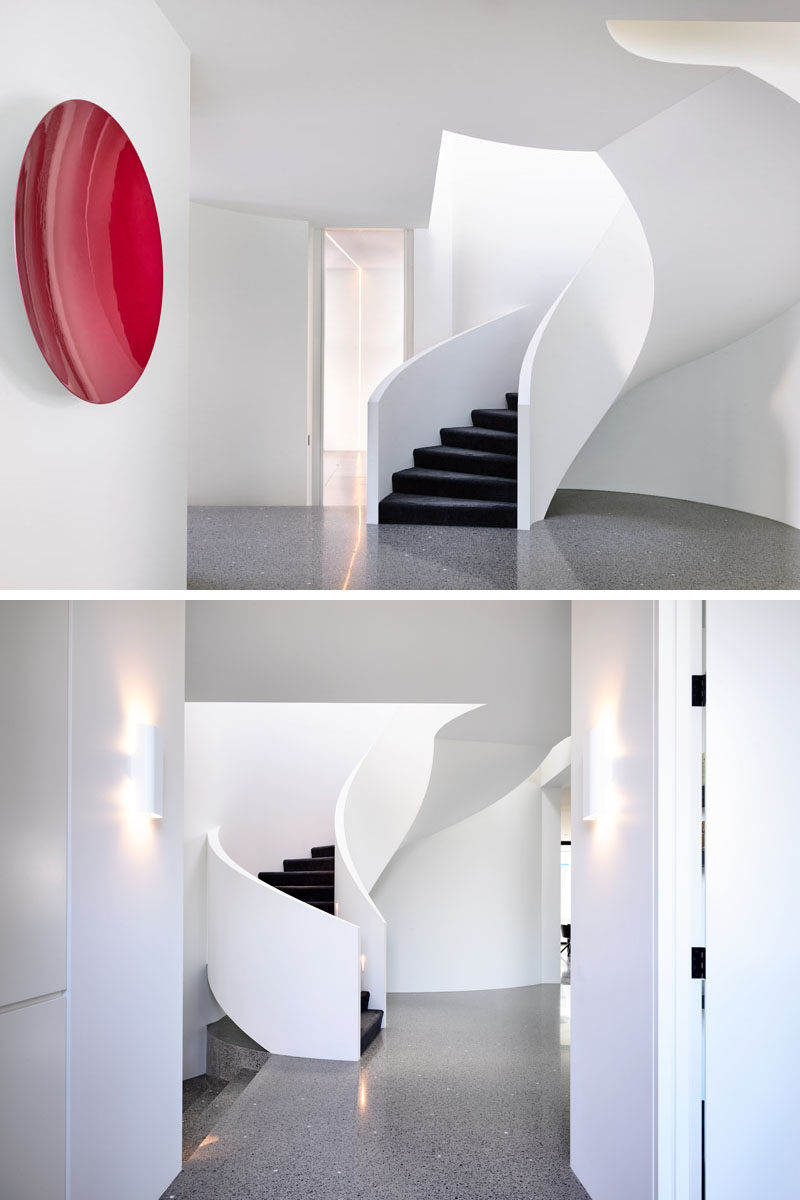 This modern house features a white spiral staircase with black stair treads. Click through to see more photos of this modern house. #Stairs #SpiralStairs #PolishedConcreteFlooring