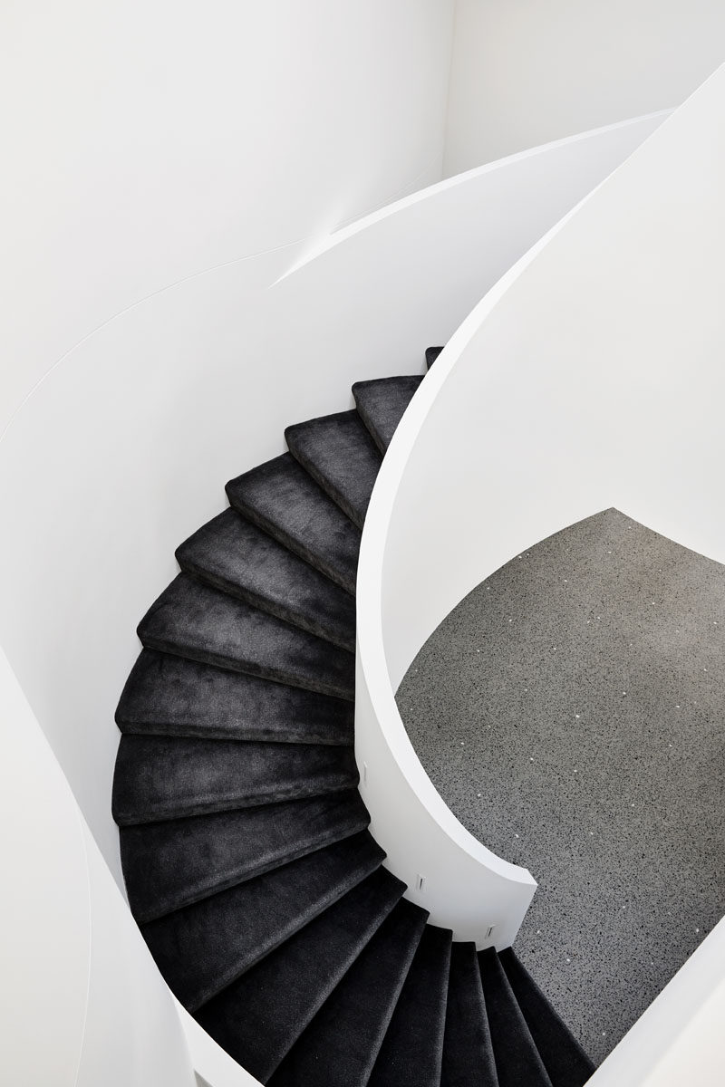 Black stair treads strongly contrast the white spiral staircase. Click through to see more photos of this modern house. #SpiralStairs #BlackAndWhite #Stairs #Staircase #BlackStairTreads