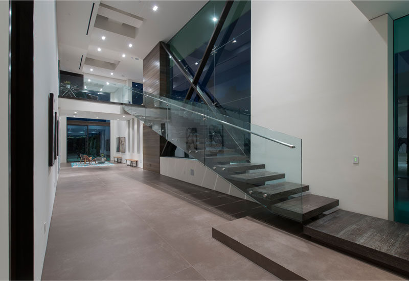 Stairs with a glass and metal handrail follow the wall and lead up to the second floor of this modern home. #ModernStairs