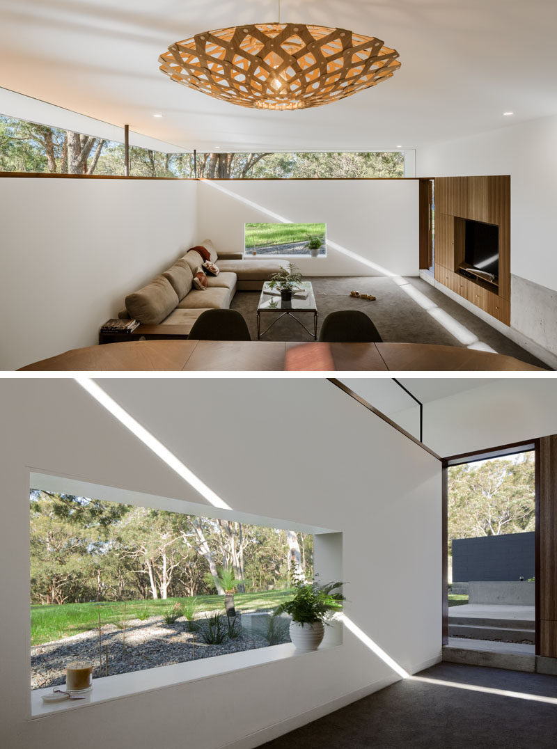 This modern house has a sunken living room with windows that allow for natural light and views of the surrounding nature. Click through to see more photos of this modern house. #SunkenLivingRoom #Windows #LivingRoom