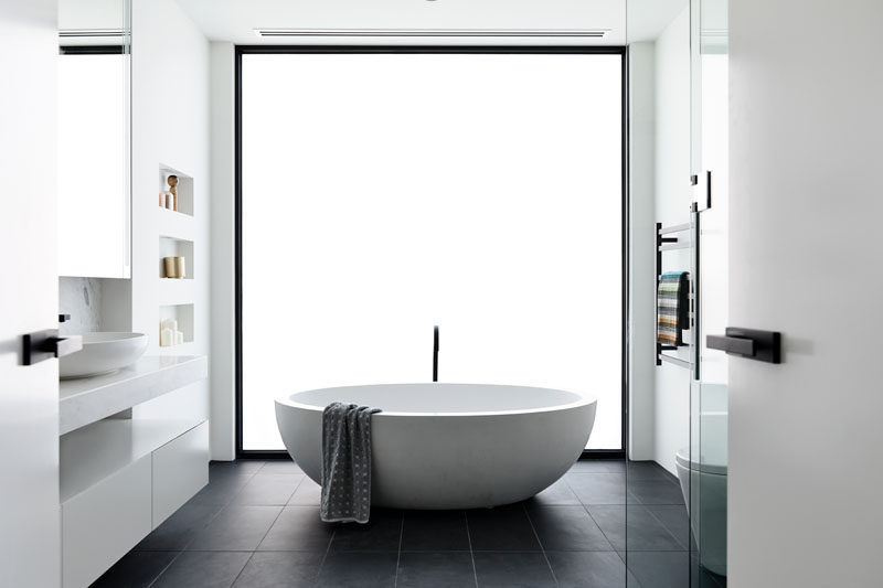 In this modern bathroom, a frosted window becomes the backdrop for the freestanding bathtub. Click through to see more photos of this modern house. #ModernBathroom #FrostedWindow #FreestandingBathtub #BuiltInShelving