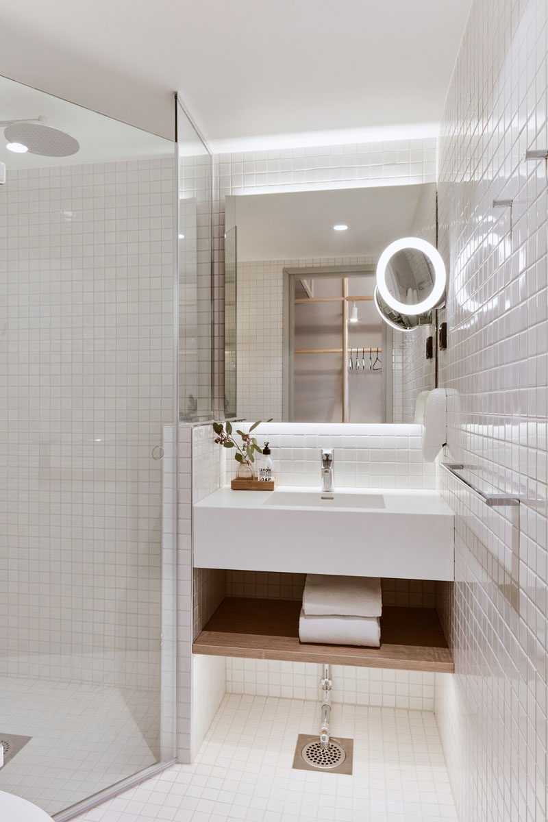 This modern bathroom has floor-to-ceiling white tiles and a backlit mirror. #WhiteBathroom