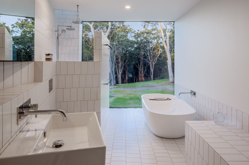 This modern white bathroom has a freestanding bathtub, rectangular white tiles, and a large picture window that frames the view. Click through to see more photos of this modern house. #WhiteBathroom #ModernBathroom #Bathroom #WhiteTiles