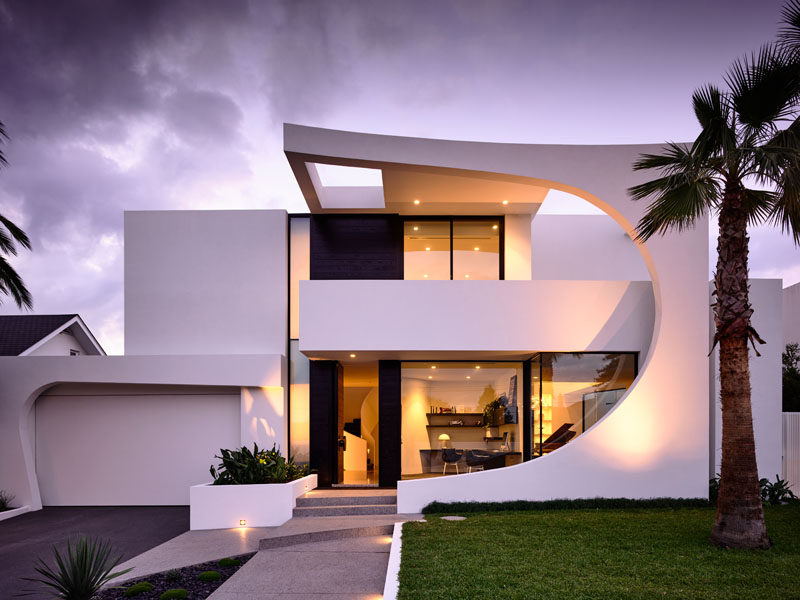 This modern house features a striking facade with a 2 storey curved section made from concrete that was cast in place. Click through to see more photos of this house. #ModernHouse #ModernArchitecture #HouseDesign #Facade #AustralianArchitecture #Landscaping
