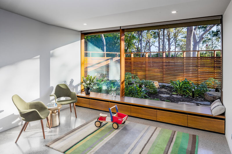 This small open room has a built-in window seat that sits next to a small garden. Click through to see more photos of this modern house. #WindowSeat #Garden #Landscaping #InteriorDesign