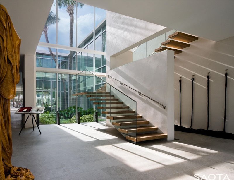 A wall of windows floods the wood and glass stairs with natural light. #Stairs #Windows