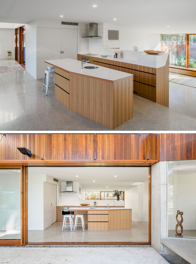 This modern kitchen has bright white countertops and light wood cabinetry. A large sliding door opens the kitchen to a covered outdoor space. Click through to see more photos of this modern house. #KitchenDesign #KitchenLayout #ModernKitchen #WoodAndWhiteKitchen