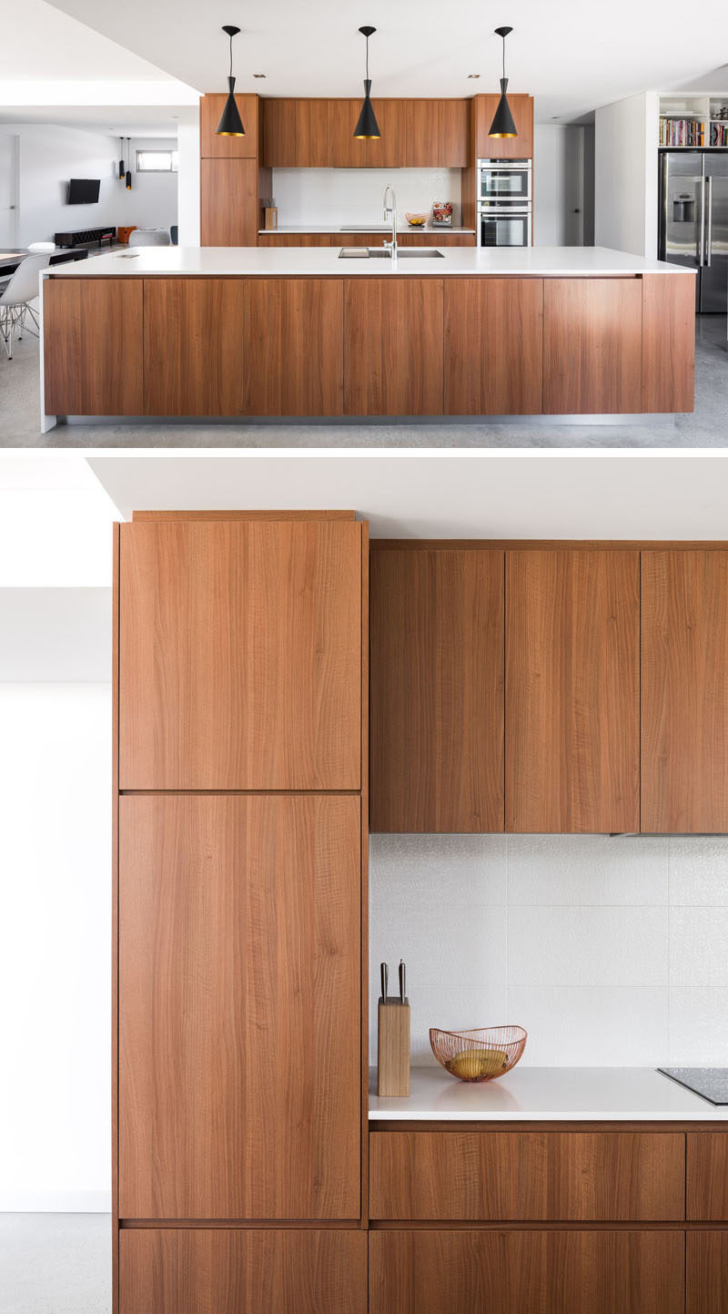In this kitchen, wood has been used for the cabinetry, while the white countertops and backsplash help to keep it bright and complete the modern look. #ModernKitchen #WoodKitchen #WhiteCounters