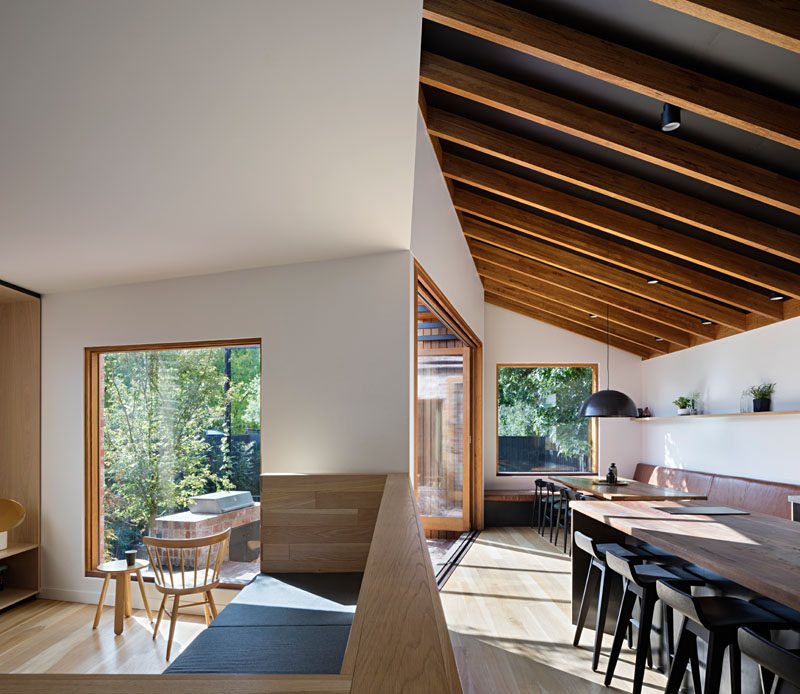 This modern extension features an oversized built-in sofa, inspired by the furniture design of Donald Judd, that separates the kitchen and living room, and provides a place for the entire family to sit and watch television together. Click through to see more photos. #HouseExtension #ModernHouseExtension #HouseAddition #OpenPlan #InteriorDesign