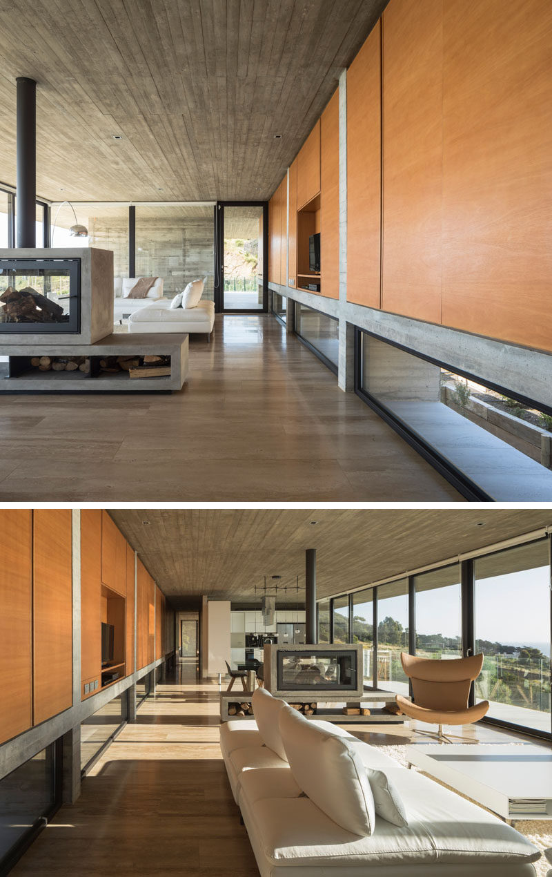Inside this modern house, the concrete structure is heavily featured, while a wall of wood cabinetry and wood flooring add a natural touch to the interior. Click through to see more photos of this modern house. #Cabinetry #ConcreteHouse #Fireplace #WoodFlooring
