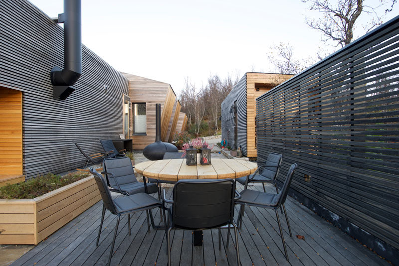 This modern house has an outdoor dining space with a fireplace and outdoor kitchen. #OutdoorSpace #Deck