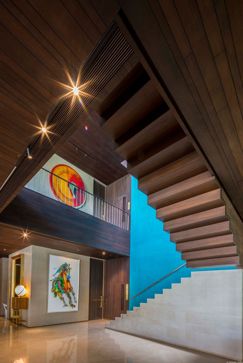 Throughout this modern house rich dark wood has been paired with rendered lime plaster walls with a stucco-like appearance. Pops of color, like the blue accent wall next to some stairs, add a touch of brightness to the interior. #InteriorDesign #WoodCeiling #Stairs