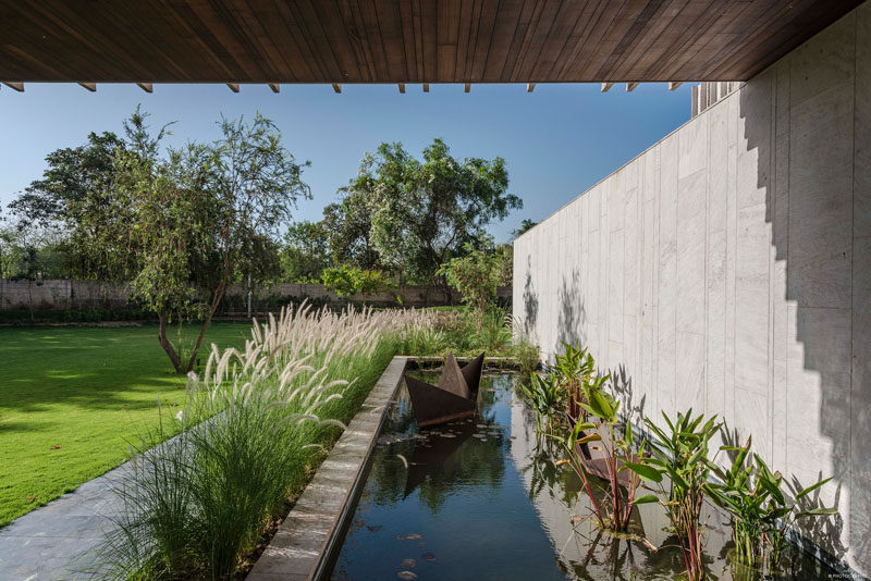 This modern house has a pond water feature that has a simple child-like sculpture of a folded sailboat. #WaterFeature #Landscaping #Garden