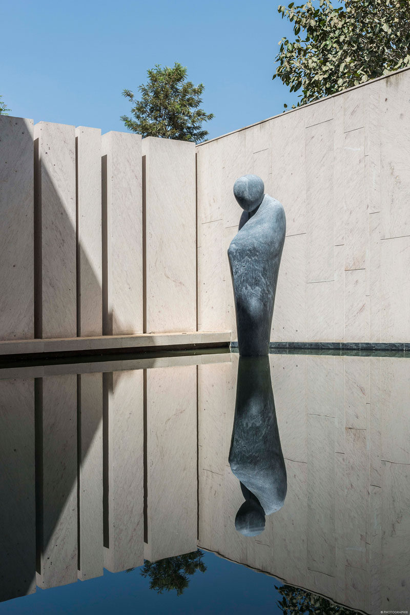 This modern water feature has a life size sculpture of a pensive monk, made from Beslana stone, that's gingerly poised on the water's surface as if levitating. #WaterFeature #Sculpture #Landscaping