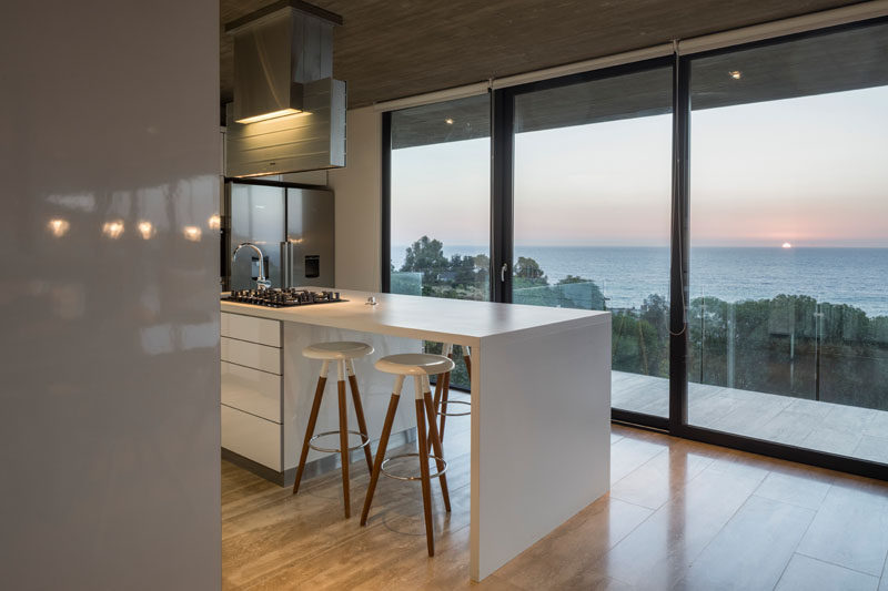 This bright white kitchen has an island and views of the water through floor-to-ceiling windows and a glass door. Click through to see more photos of this modern house. #Kitchen #WhiteIsland #Windows